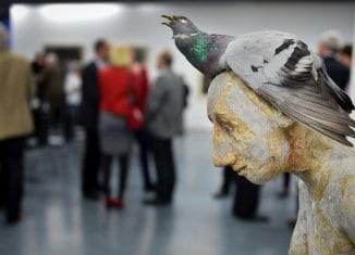 Skulptur einer jungen Frau mit einer unförmigen Taube auf dem demütig gesenkten Kopf. Foto: Andreas Greiner-Napp