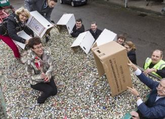 Die Unterstützer und Förderer der Kronkorken-Aktion füllen eigenhändig den Container.