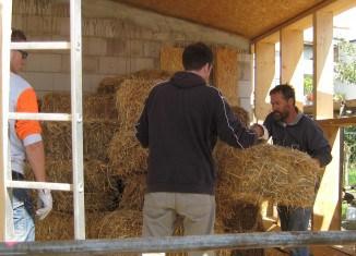 Dr. Bernd Hoppe-Dominik (rechts) und seine Mitstreiter bauen die ersten Strohballen in die Holzständer ein. Foto: FUN