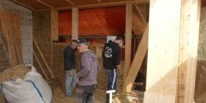 Die mit den Strohballen ausgefüllten Wände müssen von außen mit Planen vor Feuchtigkeit geschützt werden, bis sie verputzt sind. Foto: FUN