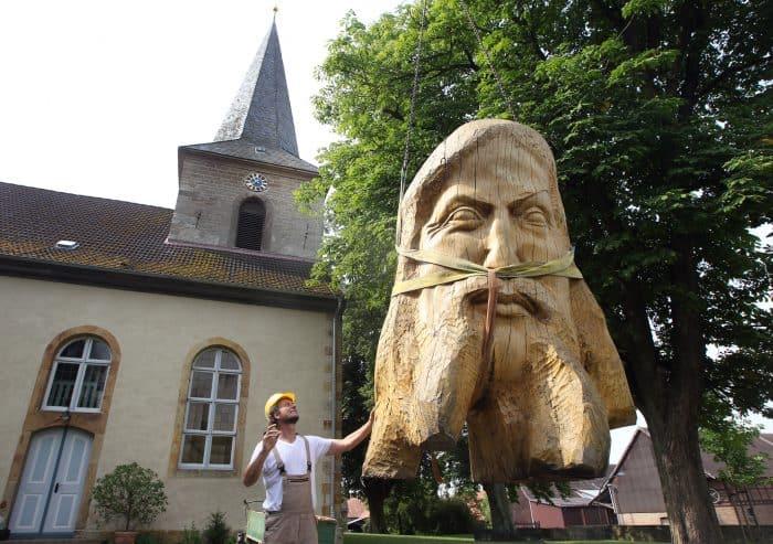 """Bildhauer Magnus Kleine-Tebbe und seine Skulptur """"Christuskopf"""" vor der Kirche in Salzgitter-Lesse. Foto: Stiftung Prüsse/Susanne Hübner"""