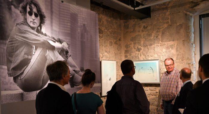 Sammler Michael-Andreas Wahle (rechts im Licht) erläutert Exponate. Foto: Prüsse Stiftung/Andreas Greiner-Napp