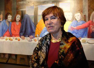 """Farbenfroh: Gudrun Brüne vor ihrer Version des """"Abendmahls"""" von Christus und seinen Jüngern."""
