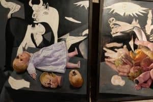 Hommage an Picasso und sein Gemälde Guernica: Zerstörte Puppen vor dem Historienbild.