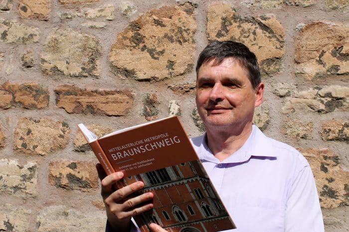 """Bauhistoriker Elmar Arnhold mit seinem neuen Buch """"Mittelalterliche Metropole Braunschweig"""". Foto: Der Löwe"""