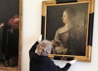 Restauratorin Heike Billerbeck hängt das Gemälde von Herzogin Christine Luise im Audienzzimmer des Schlossmuseums auf. Foto: Schlossmuseum