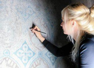 Ina Heine retuschiert die Malschichtfehlstellen mittels lasierender Technik. Foto: Melanie Specht
